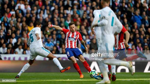 Raphael Varane of Real Madrid and Saul Niguez of Atletico Madrid battle for the ball during the La Liga match between Real Madrid and Atletico Madrid...
