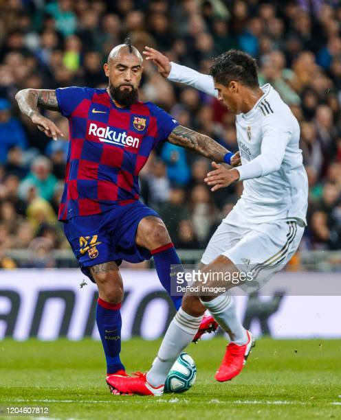 Raphael Varane of Real Madrid Arturo Vidal of FC Barcelona battle for the ball during the Liga match between Real Madrid CF and FC Barcelona at...