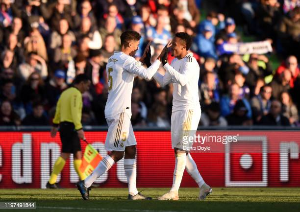 Raphael Varane of Real Madrid celebrates with teammate Eder Militao after scoring his team's second goal during the La Liga match between Getafe CF...