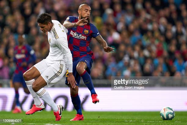 Raphael Varane of Real Madrid CF battle for the ball with Arturo Vidal of FC Barcelona during the Liga match between Real Madrid CF and FC Barcelona...