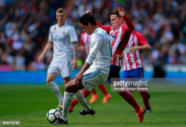 Raphael Varane of Real Madrid CF competes for the ball with Kevin Gameiro of Atletico de Madrid during the La Liga match between Real Madrid CF and...