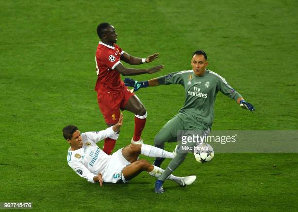Raphael Varane of Real Madrid, collides with Sadio Mane of Liverpool and Keylor Navas of Real Madrid during the UEFA Champions League Final between...