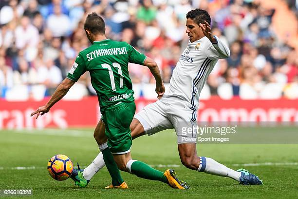 Raphael Varane of Real Madrid fights for the ball with Alexander Szymanowski of Deportivo Leganes during their La Liga match between Real Madrid and...