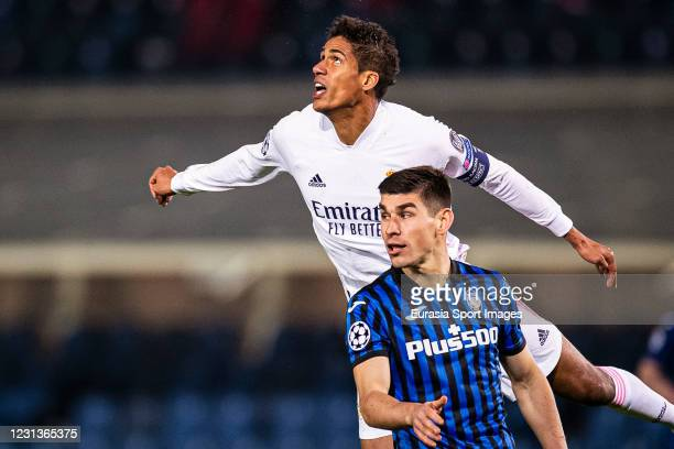 Raphael Varane of Real Madrid fights for the ball with Ruslan Malinovskyi of Atalanta during the UEFA Champions League Round of 16 match between...