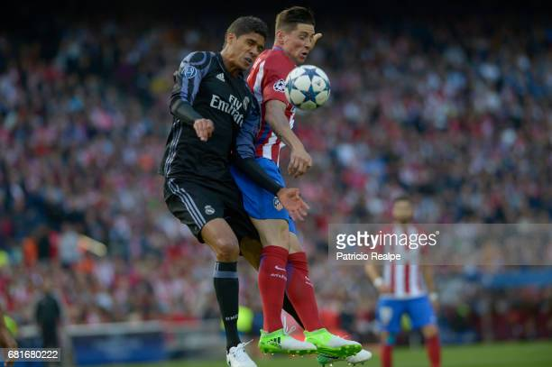 Raphael Varane of Real Madrid figths the ball with Fernando Torres of Atletico de Madrid during a match between Club Atletico de Madrid and Real...