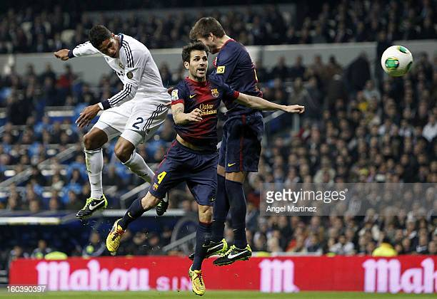 Raphael Varane of Real Madrid heads the ball to score past Cesc Fabregas and Gerard Pique of Barcelona during the Copa del Rey SemiFinal first leg...