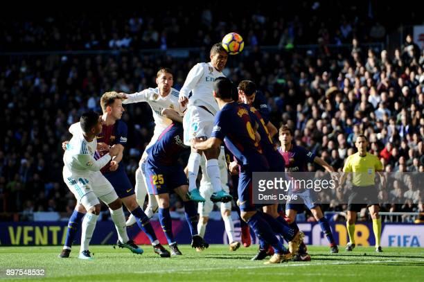 Raphael Varane of Real Madrid jumps to wina header during the La Liga match between Real Madrid and Barcelona at Estadio Santiago Bernabeu on...