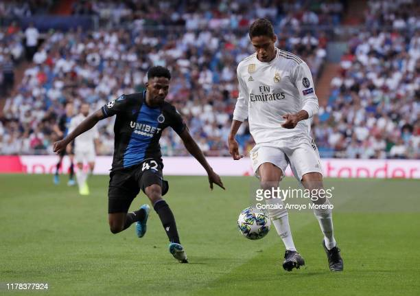 Raphael Varane of Real Madrid runs with the ball under pressure from Emmanuel Bonaventure Dennis of Club Brugge during the UEFA Champions League...