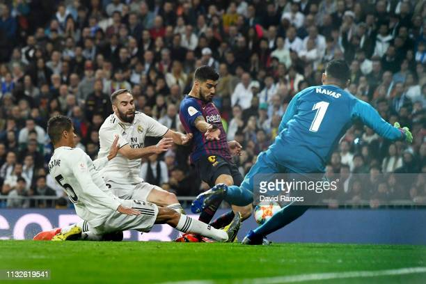 Raphael Varane of Real Madrid scores an own goal under pressure from Luis Suarez of FC Barcelona during the Copa del Rey Semi Final second leg match...