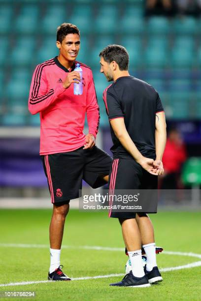 Raphael Varane of Real Madrid talks with a member of the Real Madrid backroom staff during a training session ahead of the UEFA Super Cup at A Le Coq...