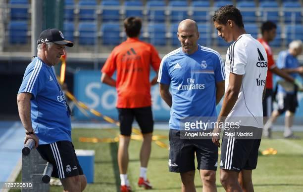 Raphael Varane of Real Madrid talks with head coach Carlos Ancelotti and assistant Zinedine Zidane during a training session at Valdebebas training...