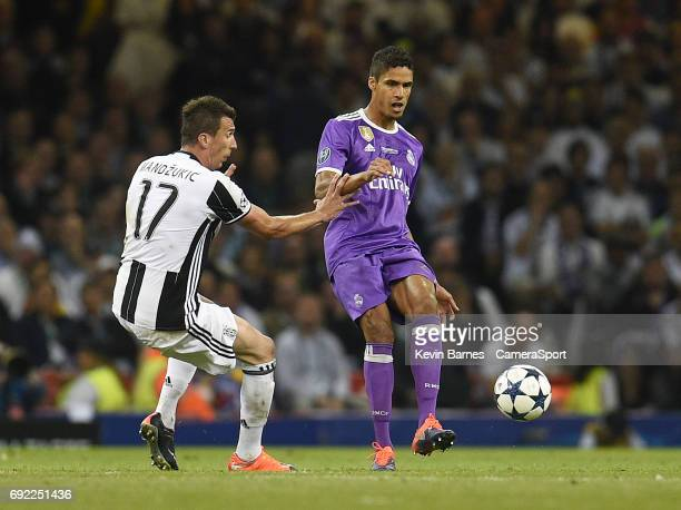 Raphael Varane of Real Madrid under pressure from Mario Mandzukic of Juventus during the UEFA Champions League Final match between Juventus and Real...