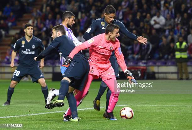 Raphael Verane of Real Madrid beats goalkeeper Jordi Masip of Real Valladolid as he scores his team's first goal during the La Liga match between...