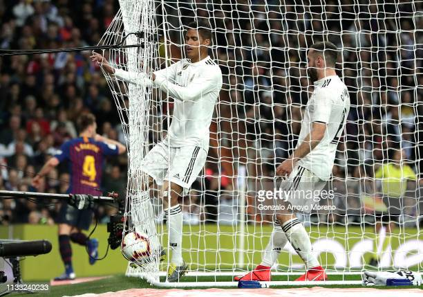 Raphael Verane of Real Madrid collects the ball out of the net after Ivan Rakitic of Barcelona celebrates scores his sides first goal during the La...