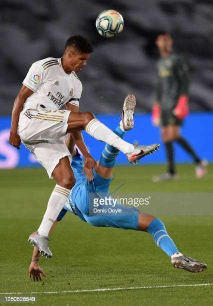 Raphaël Varane of Real Madrid CF fouls Maximiliano Gómez of Valencia CF during the Liga match between Real Madrid CF and Valencia CF at Estadio...