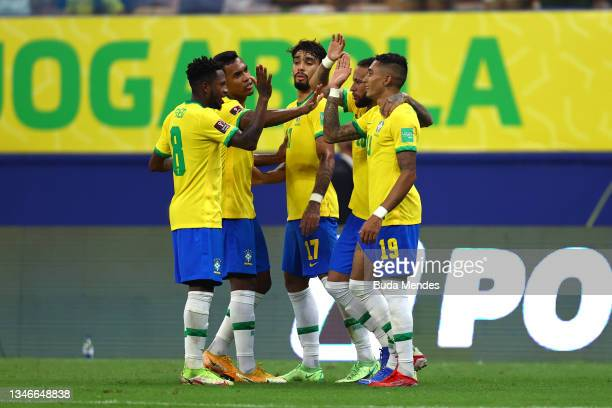 Raphinha of Brazil celebrates with teammates after scoring the third goal of his team during a match between Brazil and Uruguay as part of South...