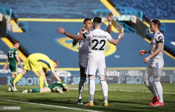 Raphinha of Leeds United celebrates their team's second goal with teammates Jack Harrison and EzgjanAlioski after Phil Jagielka of Sheffield United...