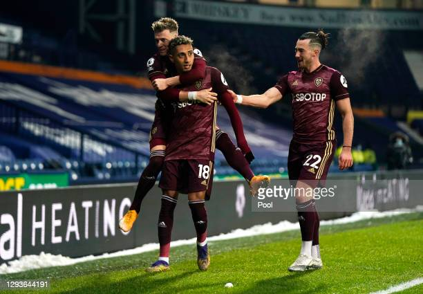 Raphinha of Leeds United celebrates with teammates Ezgjan Alioski and Jack Harrison after scoring his team's fifth goal during the Premier League...