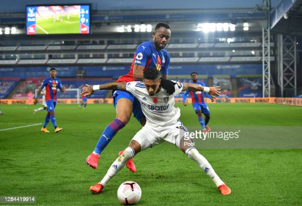 Raphinha of Leeds United is challenged by Jordan Ayew of Crystal Palace during the Premier League match between Crystal Palace and Leeds United at...