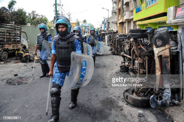 """Rapid Action Force personnel patrol on a street of Devara Jevana Halli in Bangalore on August 13 after a """"derogatory"""" Facebook post about the Prophet..."""