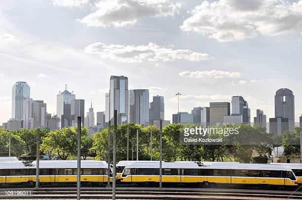 A rapid transit train with the skyline of Dallas Texas in the background
