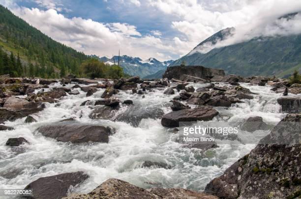 rapids in a river near mountains - stroomversnelling stockfoto's en -beelden