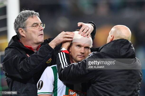 Rapid's Mario Sonnleitner receives medical treatment during the UEFA Europa League round of 32 firstleg football match between Rapid Wien and Inter...