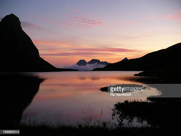 Rappensee mountain lake in the bavarian part of the Allgäu Alps. Photo taken after sunset, the sky is reflecting on the lake and there are mountains...