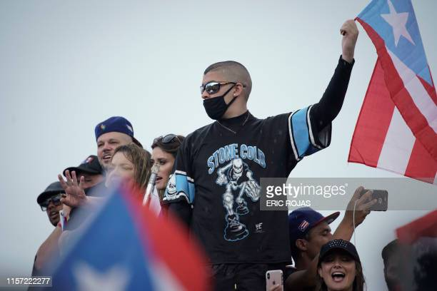 Rapper Bad Bunny waves a flag along Las Americas highway as he takes part of a national strike demanding Puerto Rico's Governor Ricardo Rossello...