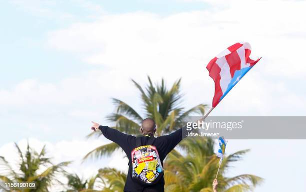 Rapper Bad Bunny waves a flag as he joins thousands of demonstrators protesting against Ricardo Rossello the Governor of Puerto Rico in front of the...