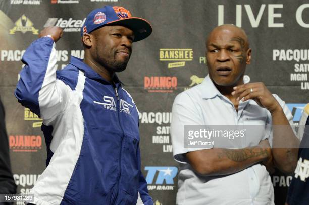 Rapper Curtis '50 Cent' Jackson waves to the crowd with former heavyweight champion Mike Tyson behind him on stage during the offical weighin for...