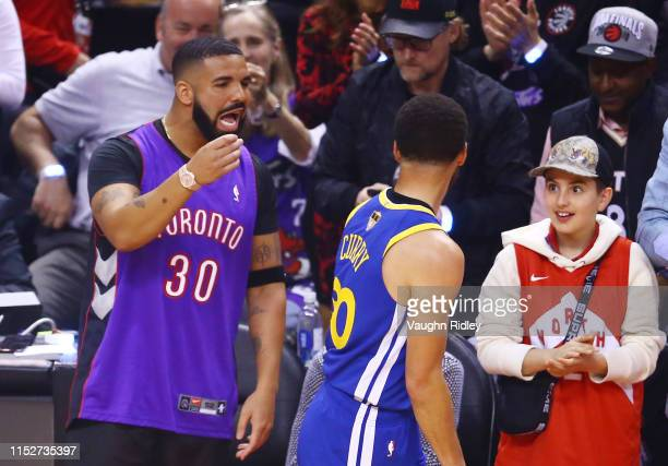 Rapper Drake and Stephen Curry of the Golden State Warriors exchange words during a timeout in the first quarter during Game One of the 2019 NBA...