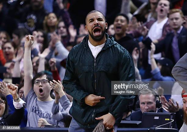 Rapper Drake shouts from his courtside seat during the second half of an NBA game between the Portland Trail Blazers and the Toronto Raptors at the...