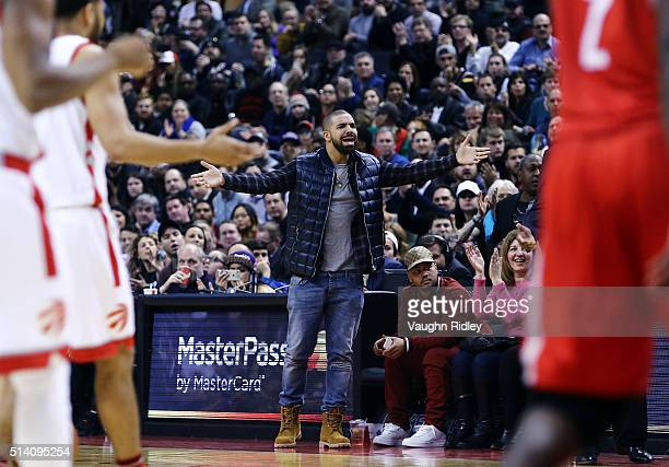 Rapper Drake shouts from his courtside seat during the second half of an NBA game between the Houston Rockets and the Toronto Raptors at the Air...