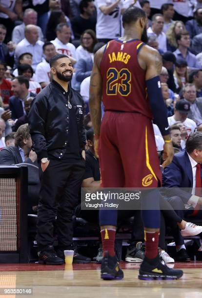 Rapper Drake smiles at LeBron James of the Cleveland Cavaliers in the second half of Game One of the Eastern Conference Semifinals against the...