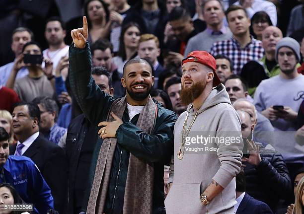 Rapper Drake smiles from his courtside seat during the second half of an NBA game between the Portland Trail Blazers and the Toronto Raptors at the...