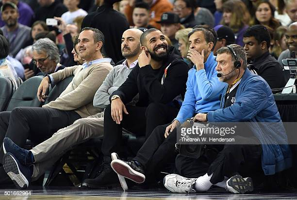 Rapper, Drake, smiling sits to the right of Sacramento Kings owner Vivek Ranadive' during an NBA basketeball game between the Kings and Houston...