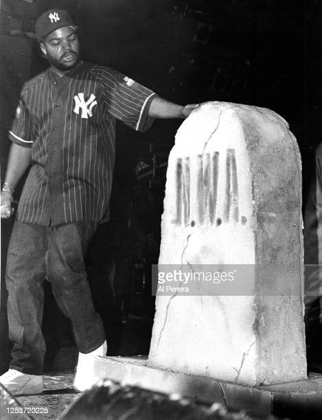 Rapper Ice Cube performs in a New York Yankees Starter brand jersey and cap next to a prop tombstone for his old band, N.W.A., at The Apollo Theater...