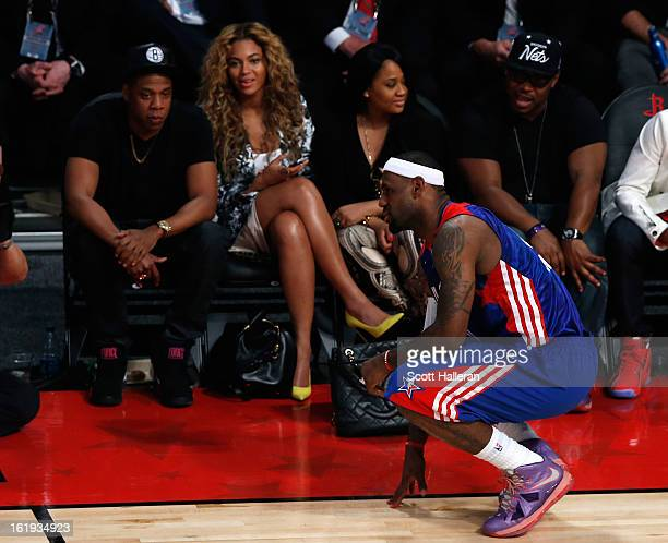 Rapper JayZ and Beyonce look over at LeBron James of the Miami Heat and the Eastern Conference during the 2013 NBA AllStar game at the Toyota Center...