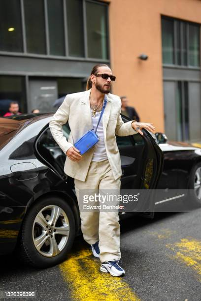 Rapper Julien Schwarzer aka SCH wears sunglasses, golden necklace, a beige blazer jacket, a blue crossbody Jacquemus bag, a white t-shirt, beige...