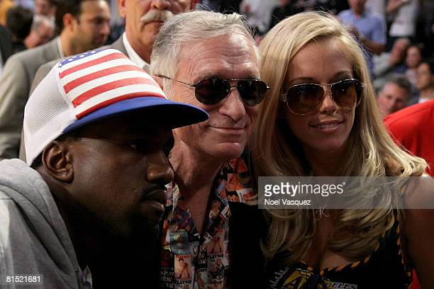 Rapper Kanye West and television personalities Hugh Hefner and Kendra Wilkinson pose during Game Three of the 2008 NBA Finals between the Boston...