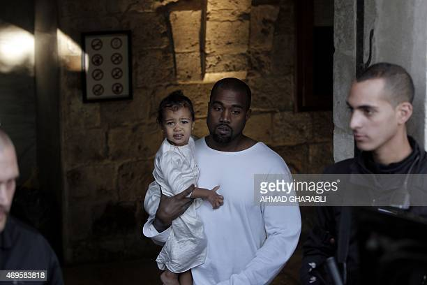 US rapper Kanye West husband of US reality TV star Kim Kardashian carries their daughter North following a reported baptism ceremony at the Armenian...