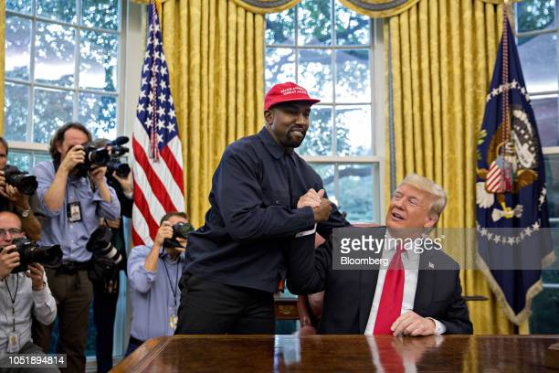 Rapper Kanye West left shakes hands with US President Donald Trump during a meeting in the Oval Office of the White House in Washington DC US on...