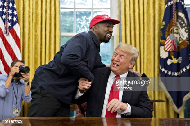 Rapper Kanye West, left, shakes hands with U.S. President Donald Trump during a meeting in the Oval Office of the White House in Washington, D.C.,...