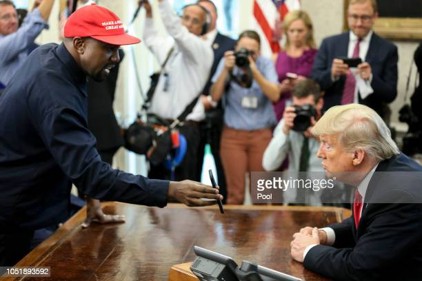 Rapper Kanye West left shows a picture of a plane on a phone to US President Donald Trump during a meeting in the Oval office of the White House on...
