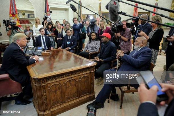 Rapper Kanye West second right flanked by NFL Hall of Famer Jim Brown right speaks during a meeting with President Donald Trump left in the Oval...