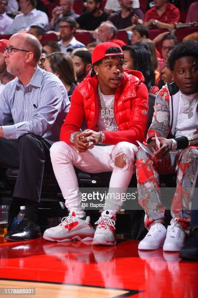 Rapper Lil Baby watches during a game between the Oklahoma City Thunder and the Houston Rockets on October 28 2019 at the Toyota Center in Houston...