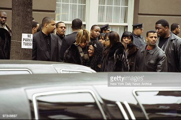 Rapper Lil' Kim is consoled by Mary J Blige after she breaks down during funeral procession for Notorious BIG