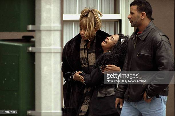 Rapper Lil' Kim of Junior Mafia is consoled by Hip Hop Queen Mary J Blige following funeral services for Notorious BIG outside Campbell Funeral Home