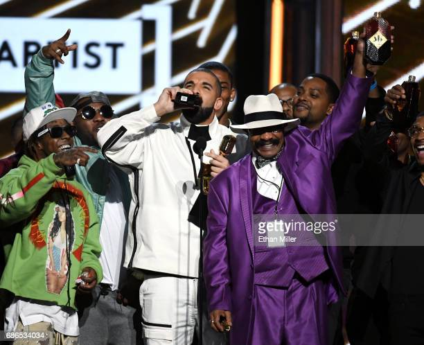 Rapper Lil' Wayne looks on as recording artist Drake accepts the Top Artist award onstage with his father Dennis Graham during the 2017 Billboard...